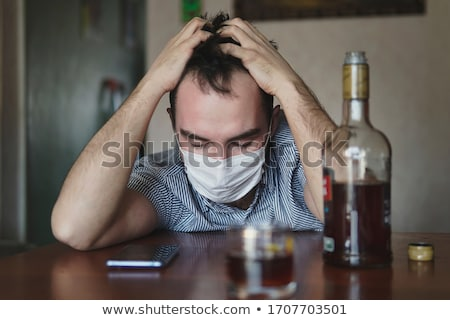 man with smartphone and bottle of alcohol at home Stock photo © dolgachov