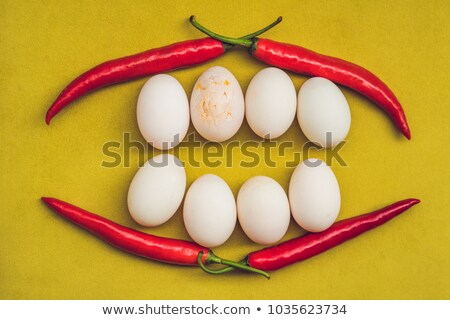 Eggs and red pepper in the form of a mouth with teeth. One of the teeth is sick in the form of a cra Stock photo © galitskaya