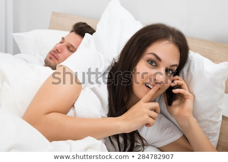 Woman Talking On Cellphone While Her Husband Sleeping On Bed Stock photo © AndreyPopov