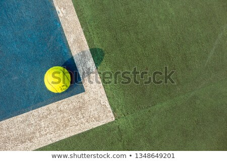 Fluorescent yellow tennis ball in the corner on blue acrylic surface Stock photo © Kzenon