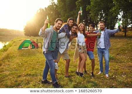 happy friends clinking drinks at summer park Stock photo © dolgachov