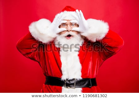 happy santa in white and red costume and eyeglasses looking at you stock photo © pressmaster