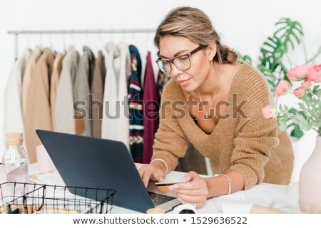 Young woman in casual beige woolen pullover making order in online shop Stock photo © pressmaster