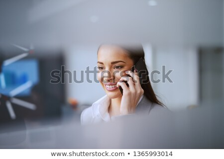 Pretty young businesswoman in formalwear looking at you while sitting by desk Stock photo © pressmaster