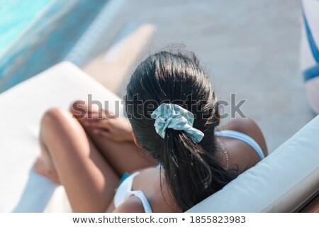 Jovem bela mulher relaxante espreguiçadeira piscina foco Foto stock © GVS