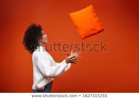 Happy young african woman catching a pillow Stock photo © deandrobot