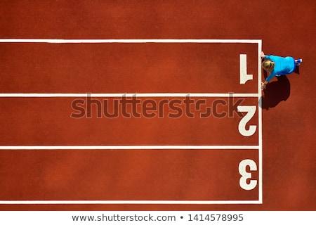 Female athlete in starting position on track Stock photo © darrinhenry