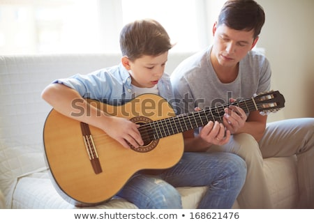 father teaching son how to play the guitar stock photo © photography33