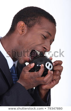 Man trying to bite open a piggy bank Stock photo © photography33
