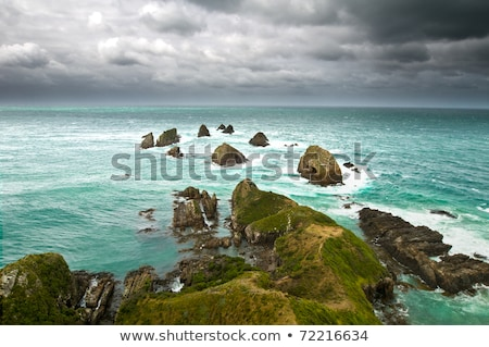 Cliffs under thunder clouds and turquoise ocean Stock photo © 3523studio