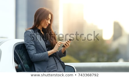 Woman in suit with mobile phone outdoors stock photo © photography33