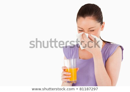 Good looking woman holding a glass of orange juice and sneezing while standing against a white backg stock photo © wavebreak_media