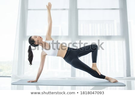 woman in a traditional stretching yoga pose at home or gym stock photo © hasloo