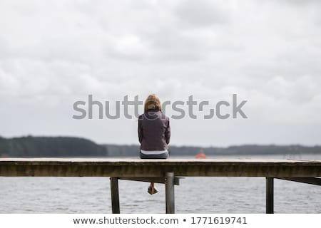young lady sitting on the jetty  Stock photo © Klinker