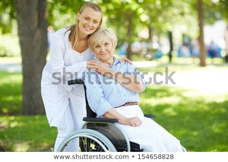 Doktor bakıcı yaşlı gülen kamera genç Stok fotoğraf © belahoche