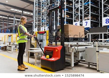 Worker with fork pallet truck stacker in warehouse Stock photo © wavebreak_media