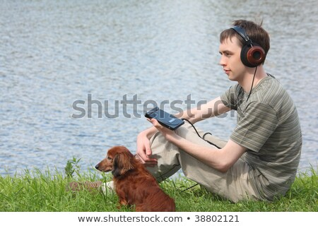 Young man liistens music in headphones sits on grass ashore Stock photo © Paha_L