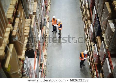 worker taking inventory in logistics warehouse stock photo © kzenon