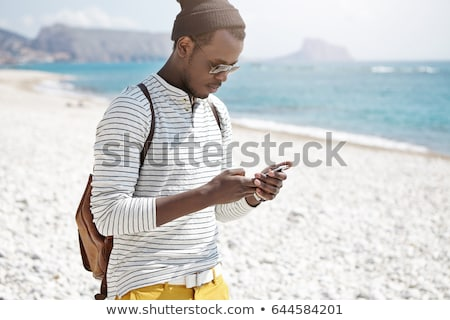 Male tourist using mobile phone at seaside on summer holiday Stock photo © stevanovicigor