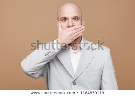 Young businessman covering his mouth with his hand Stock photo © gsermek