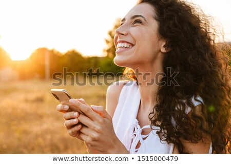 фото молодые улыбающаяся женщина длинные волосы используя ноутбук Сток-фото © deandrobot