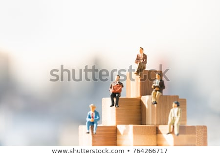 Wooden figurine stepping on stack of coins Stock photo © wavebreak_media