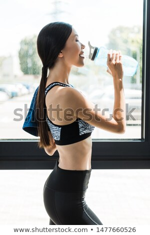 Side view of sports woman drinking water with closed eyes Stock photo © deandrobot