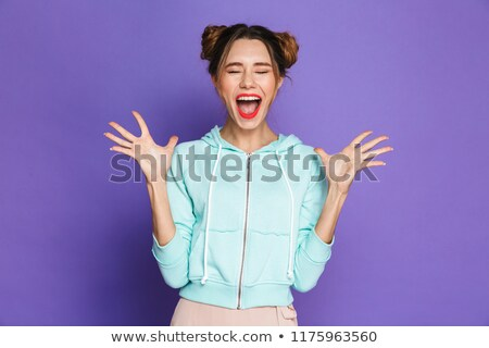 Portrait of amazed woman with two buns screaming and raising arm Stock photo © deandrobot