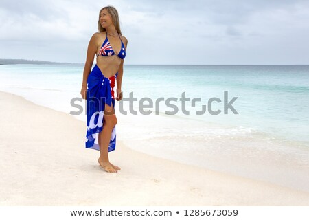 Woman on beach with Aussie flag draped around her Stock photo © lovleah