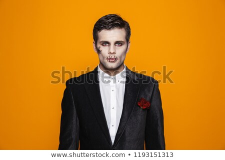 Photo of terrifying zombie bridegroom wearing classical suit and Stock photo © deandrobot