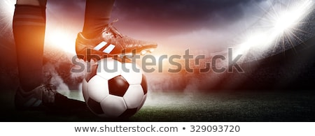 close up of young soccer player kicking ball on soccer field stock photo © matimix