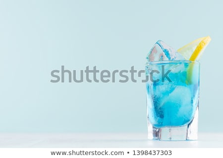 Glass with a bright blue lagoon cocktail on the table by the poo Stock photo © dashapetrenko