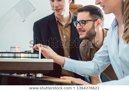Couple testing a Hi-Fi system in the store with the salesman explaining Stock photo © Kzenon