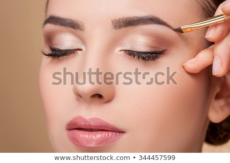 Make up artist working on woman's eyebrows in salon Stock photo © Kzenon
