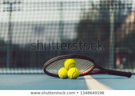 Three tennis balls on a professional racket on acrylic blue surface Stock photo © Kzenon