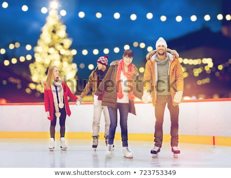 happy friends on skating rink outdoors Stock photo © dolgachov