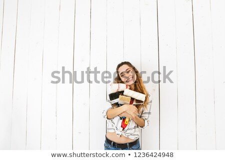 Image of cheerful woman 20s holding rollers and brushes, while p Stock photo © deandrobot