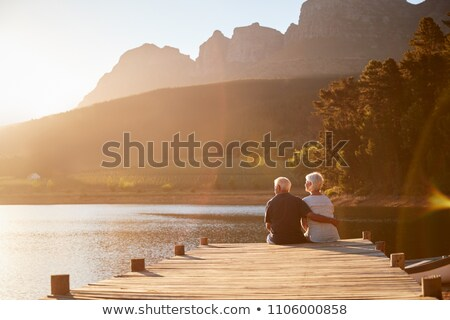 Rear view of active senior couple sitting together on the bench and smilling at the camera in the pa Stock photo © wavebreak_media