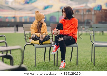 Outdoor shot of fashionable child sits crossed legs at chair, has friendly talk with older sister, p Stock photo © vkstudio
