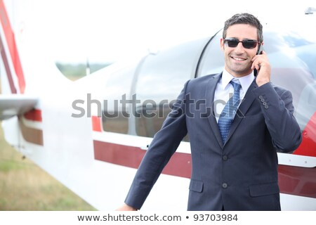 Executive chatting on the phone in front of a small aeroplane Stock photo © photography33