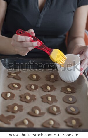 glazing cookies before backing on backing paper in a tray Stock photo © 3523studio