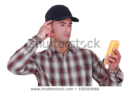 Puzzled tradesman staring at his multimeter Stock photo © photography33