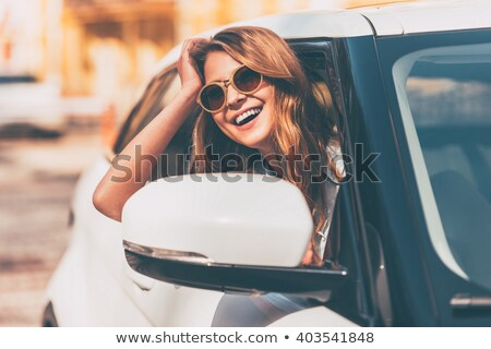 Young woman looking ahead of her while and smiling sitting against the trunk of a tree Stock photo © wavebreak_media