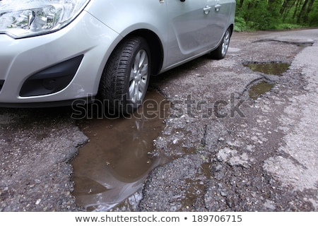 Car driving on a potholed dirt road Stock photo © jrstock