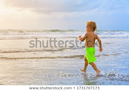 Child running on water at ocean beach. Stock photo © ryhor