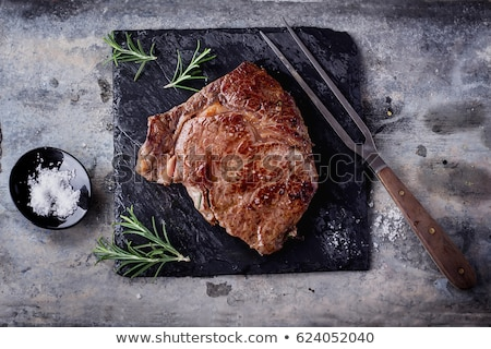 Stock photo: Grilled beef steak topped with butter and rosemary