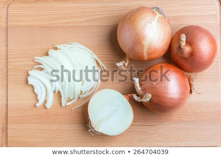 whole and sliced onions on chopping board stock photo © frannyanne