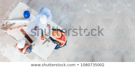 Young woman in helmet with a saw on a white background Stock photo © vlad_star