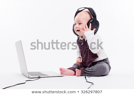 cute baby sitting in front of a laptop wearing headphones on a w stock photo © traimak