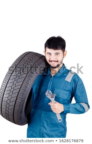 Young hispanic mechanic with tyre and spanner. Stock photo © RAStudio